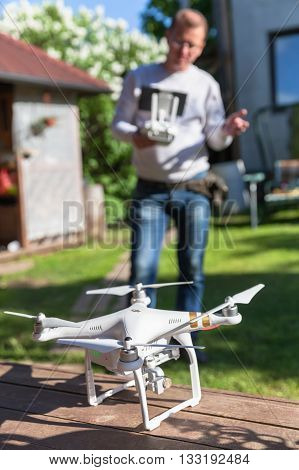 St. Petersburg Russia - May 4 2016: Drone quadrocopter Phantom 3 Professional with high resolution camera by DJI stands on a wooden floor blurred man with remote control on a background