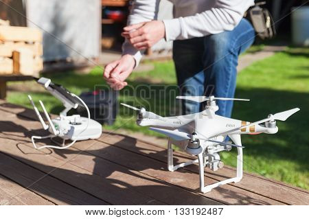 St. Petersburg Russia - May 4 2016: Drone quadrocopter Phantom 3 Professional with high resolution camera by DJI stands on a wooden floor blurred pilot with remote control on a background