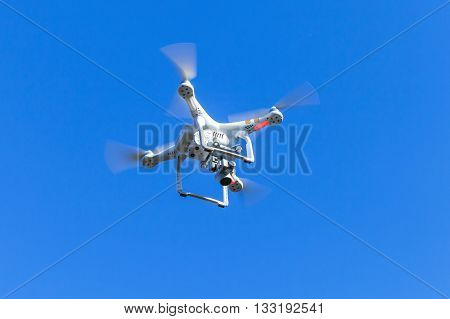 St. Petersburg Russia - May 4 2016: Drone quadrocopter Phantom 3 Professional with high resolution digital camera designed by the Chinese company DJI soars in blue sky