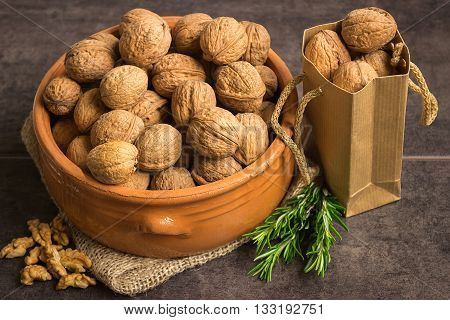 Walnuts in a ceramic pot on a dark background with rosemary