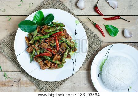 Stir fried pork and red curry paste with string bean on wood backgroundTop view