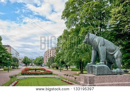 PORI, FINLAND - JULY 6, 2013:  Pori Bear,  This bronze sculpture was built in 1938 and symbolizes the life of the province and the town. On the background is The Town Hall Park