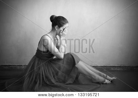 Crying woman in a ballet dress sitting on the shabby floor. Black and white shot. Vignette is added.