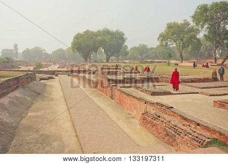 SARNATH, INDIA - JAN 5, 2016: Buddhist monk in red dress walking past ruined temple in sacred place with green trees on January 5, 2016. Sarnath is where Gautama Buddha first taught the Dharma at 500 BC.