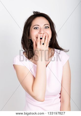 Close up portrait happy young beautiful brunette woman closes mouth by hand. Shocked surprised stunned. Positive human emotion. girl flirting concept.