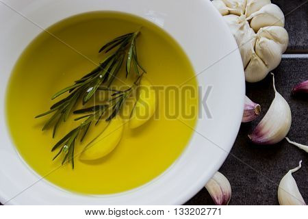 Extra virgin olive oil flavored with garlic and rosemary in a white piala