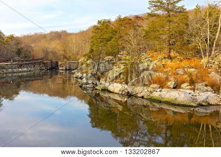 A path along canal in the Great Falls National Park Virginia USA. Scenic fall forest with reflections near the old lock.