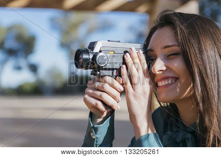 Female photographer holding old camera and smiling