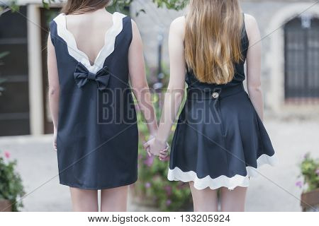 back view of two young women in stylish black and white dresses