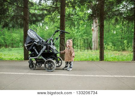 Baby in sitting stroller on nature. Adorable one year-old child with a stroller walk in a green summer forest. Cute child standing next to his stroller