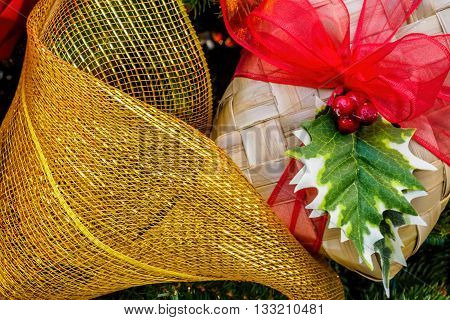 Christmas decorative wicker box, red ribbon and artificial hollies - A closeup view from a Christmas tree. The box is placed beside a golden yellow netting ribbon.