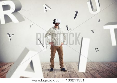 Smiling Caucasian bearded man in casual clothes and headphones is wearing virtual reality glasses and standing surrounded by flying letters in empty room with white wall and wooden floor