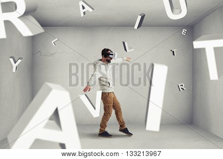 Man in virtual reality glasses is stepping carefully between flying letters composing word combination