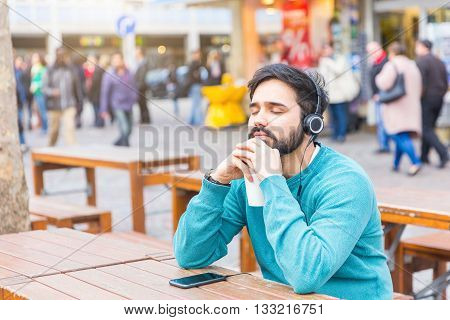 Young man relaxing and listening to music with headphones in the city. He is keeping his eyes closed while holding a cup of coffee. There are blurred people on background.