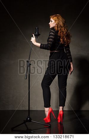 Back view of red-haired singer standing near mic in red high heels.Studio shot