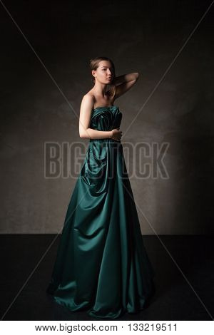 Model in beautiful long dress with arm raised looking down.Studio shot