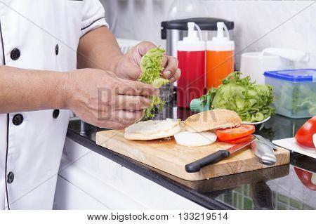 Chef prepared slice of lettuce on the Hamburger bun /Cooking Hamburger concept