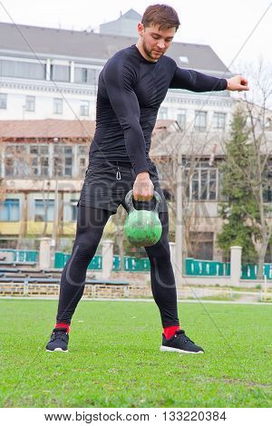 young attractive man athlete do strength training with weights at the stadium in a black tracksuit