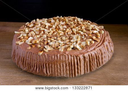 chocolate cake with toffee and peanuts on a wooden background