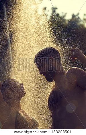 Young couple taking a shower on the beach after swimming