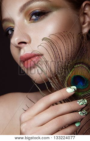 Beautiful girl with bright makeup, manicure design and peacock feather on her face. Art nails. Photos shot in the studio.
