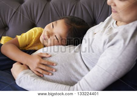 Pregnant Mother Relaxing On Sofa With Daughter