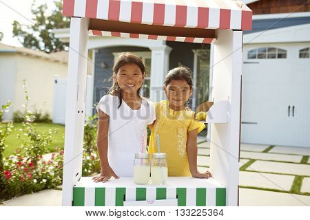 Portrait Of Two Girls At Home Made Lemonade Stall