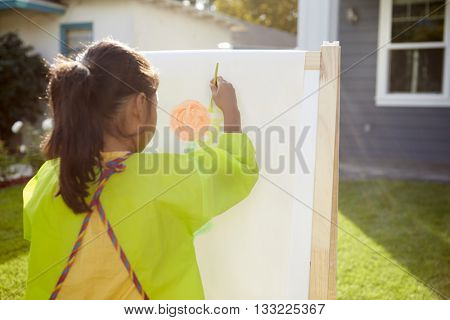 Rear View Of Girl Painting Picture In Garden