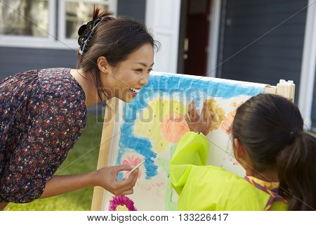 Mother And Daughter Painting Picture In Garden Together