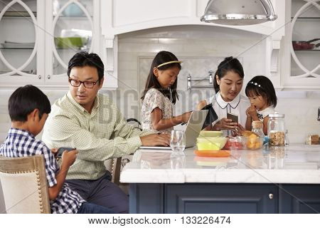 Family At Breakfast Using Digital Devices