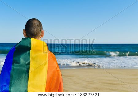 closeup of a young caucasian man seen from behind wrapped in a rainbow flag looking at the ocean