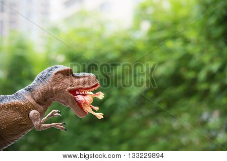 gigantic tyrannosaurus catches a smaller dinosaur in front of trees and building