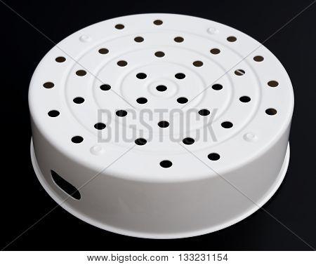bottom of white plastic steamer on black background