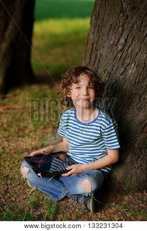 The boy of 8-9 years sits leaning against a tree and holds the tablet in hand.The laddie with a blond curly hair looks in a camera. Jeans are torn on a lap.Behind the back there is a thick tree trunk