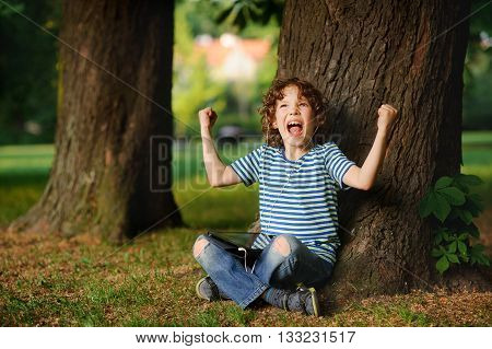 The indignant boy sits under a tree with tablet on lap. He sits having crossed legs. Jeans are torn on knees. On a face angry expression. The boy has raised hands with the clenched fists up.