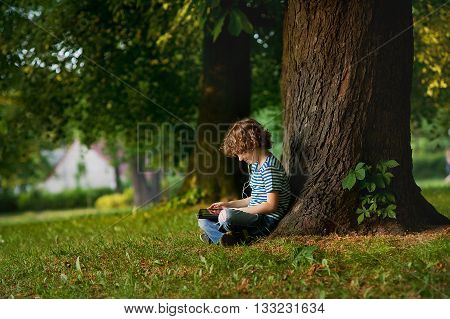 The little fellow sits under a big tree and looks at the tablet screen. On his face thoughtful smile. The boy sits sideways to a camera.He absolutely small against a huge trunk