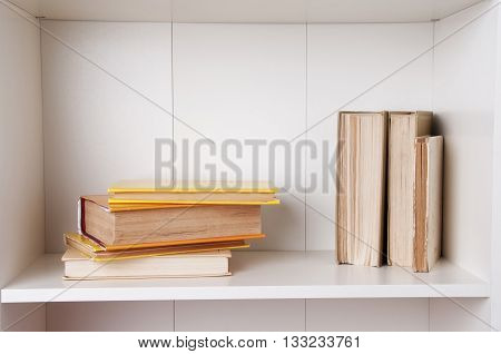 Old books or text books on wooden bookshelf. Books and reading are essential for self improvement gaining knowledge and success in our careers business and personal lives.