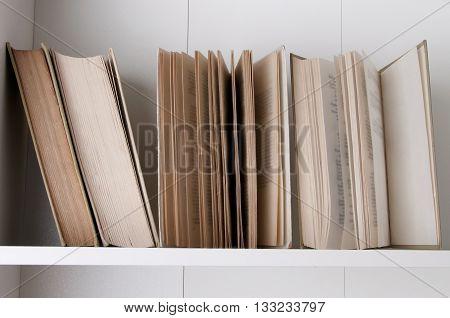 Open book, stack of hardback books on wooden bookshelf.