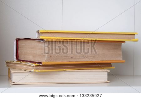 Stack of hardback books on wooden bookshelf. Back to school. Copy space.