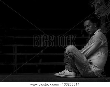 Black and white portrait of lonely / disappointed / unhappy businessman sitting on the stairs in black corner (Dark tone)