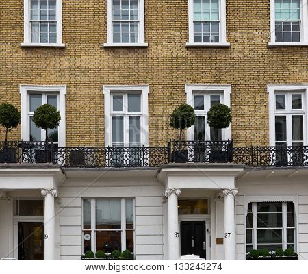 LONDON - FEBRUARY 08, 2016: Ornate exterior wrought iron balcony with topiary trees over two porticoes below in a historical building front facade. February 08, 2016 in London, UK.