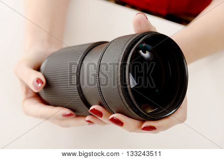 close-up of the hands of a woman with a camera lens