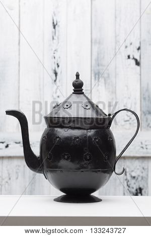 Ancient historic iron kettle for boiling hot water. Kettle of black colour represented on table in studio. White wooden background.