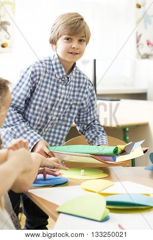 Little cute boy on art classes. Preparing colorful;l papers to create some art