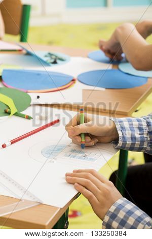 Close-up of little boy's hands coloring the picture of house during art classes at school