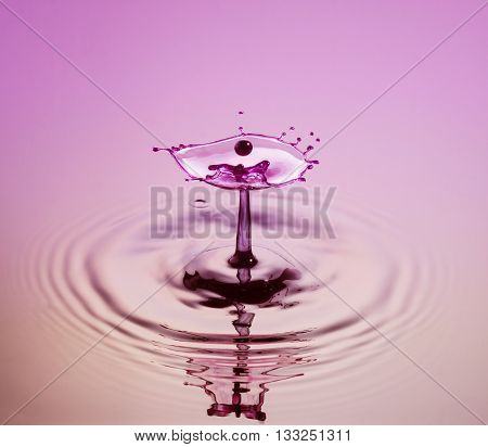 Water drop photography one or two drops of water dropped from height into a tray filled with water and captured as they hit the water or collide with each other.