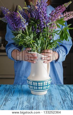 Woman's hands styдing together a bouquet on table