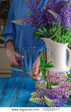 Woman's Hands Tying Together A Bouquet Of Lupines