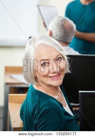 Happy Senior Woman At Desk In Computer Class