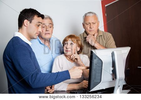 Tutor Assisting Senior People In Using Computer At Classroom